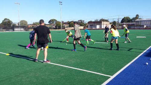 coach supervising hockey players training